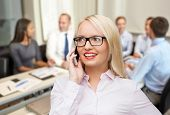 business, teamwork and people concept - smiling businesswoman, student or secretary in eyeglasses calling on smartphone over office and group of colleagues background