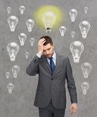 business, education, emotional pressure and people concept - handsome businessman having headache over concrete background with light bulbs
