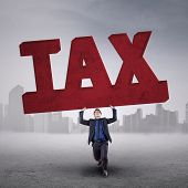 Man Lifting A Tax Sign Outdoors