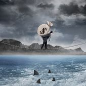 image of sack dollar  - Male entrepreneur walking on the rope above the sea while carrying a money sack - JPG