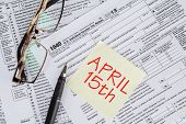 stock photo of income tax  - Closeup of the deadline time of tax with the tax form and glasses - JPG