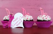 foto of stilettos  - International Womens Day March 8 cupcakes with high heel stiletto fondant shoes on vintage pink wood background with greeting tag - JPG
