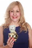 A Happy Mature Blonde Woman Holds a GOLD Piggy Bank with a One Hundred Dollar Bill sticking out through the top. Isolated on white with room for your text