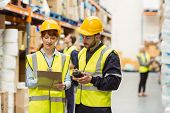 Warehouse manager talking with worker in a large warehouse