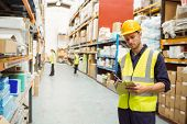 Focused warehouse worker with clipboard in a large warehouse