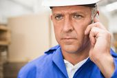 foto of hard-on  - Worker in hard hat using mobile phone in the warehouse - JPG