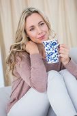 Thoughtful blonde on couch holding cup of coffee at home in the living room