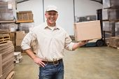 Smiling worker holding cardboard box in a large warehouse