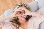 Smiling blonde making heart with her hands at home in the living room