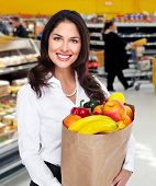 Young beautiful woman with a grocery bag in supermarket