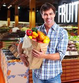 Handsome man with fruits bag in grocery store.