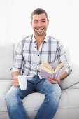A smiling man seating in the sofa with a mug reading a book