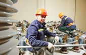 Electricians lineman repairman worker at huge power industrial transformer installation work