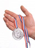 Award winner hand holding a silver medal isolated on white background.