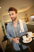 Waiter in coffee shop holding service tray
