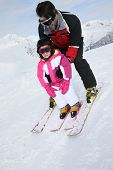 Daddy with little girl skiing down slope