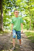 Cute Boy Walking Through The Forest