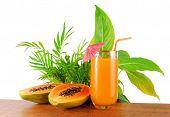 image of papaya fruit  - papaya fruit and glass of juice and exotic leaves - JPG