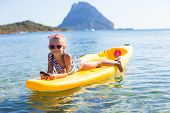 Adorable little girl kayaking in blue sea during summer vacation