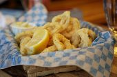 Calamari and lemon in a straw basket with paper