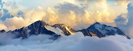 picture of freezing  - alpine landscape with peaks covered by snow and clouds - JPG
