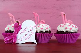 foto of stiletto  - International Womens Day March 8 cupcakes with high heel stiletto fondant shoes on vintage pink wood background with greeting tag - JPG
