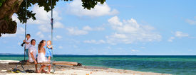 foto of family vacations  - Family of four having fun on tropical beach - JPG