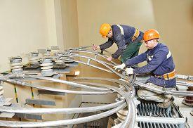 foto of transformer  - Electricians lineman repairman worker or installers at huge power industrial transformer installation work - JPG