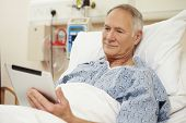 stock photo of hospital patient  - Senior Male Patient Using Digital Tablet In Hospital Bed - JPG