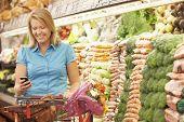 image of supermarket  - Woman Using Mobile Phone In Supermarket - JPG