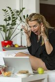 image of hysterics  - Young hysterical blonde woman screaming at laptop - JPG