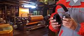 stock photo of factory-worker  - Worker with protective headphone at man hands at industrial factory - JPG