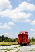 stock photo of caboose  - An old red caboose on a track under blue skies - JPG
