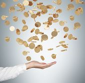 picture of golden coin  - Close up of the open palm and falling golden dollar coins from the ceiling - JPG