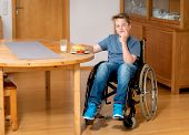 pic of bap  - disabled boy in wheelchair is eating in the living room - JPG