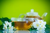 pic of jasmine  - jasmine tea in a teapot with a branch of jasmine on a green background - JPG