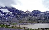 foto of snow capped mountains  - High mountain landscape at Bernina Pass in Switzerland; snow-capped mountains and steep rocks, a small mountain lake; mostly cloudy sky ** Note: Soft Focus at 100%, best at smaller sizes - JPG