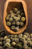stock photo of peppercorns  - Green Peppercorns on a wooden background - JPG