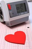 stock photo of electrocardiogram  - Instrument for measuring blood pressure and red heart shape on electrocardiogram graph ekg heart rhythm medicine concept - JPG