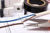 stock photo of insulator  - Cable cutter electric wire and fuse insulating tape lying on construction drawing of house accessories for engineer jobs repair of cable - JPG