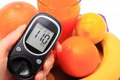 picture of immune  - Hand with glucose meter fresh ripe natural fruits and glass of juice concept for diabetes healthy nutrition and strengthening immunity - JPG
