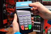 picture of debit card  - Hand of woman paying with contactless credit card with NFC technology in an electrical shop credit card reader payment terminal finance concept - JPG