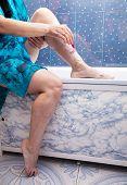 stock photo of shaving  - woman in a blue bathrobe shaving leg sitting in the bathroom - JPG