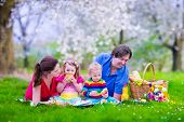 image of healthy eating girl  - Young family with kids having picnic outdoors - JPG