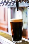 foto of draft  - Bartender pouring draft beer in the bar. ** Note: Shallow depth of field - JPG