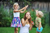 stock photo of blowers  - mother and her children play with bubble blower on green lawn