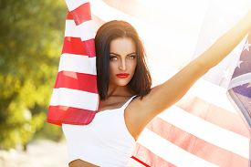 stock photo of independent woman  - Sexy woman with usa flag outdoor star spangled banner 4th july independence day - JPG