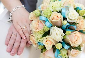 stock photo of wedding  - Hand of the groom and the bride with wedding rings at a wedding party - JPG