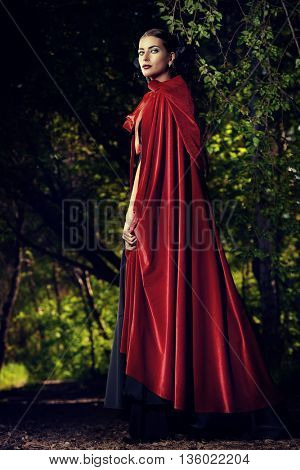 Beautiful brunette woman in black old-fashioned dress and red cloak walking in the thicket of the ma