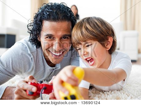 poster of Excited little boy and his father playing video games lying on the floor in the living-room